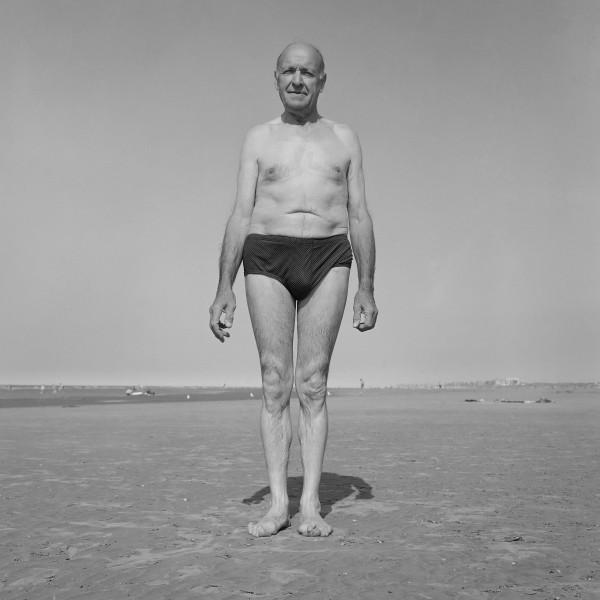 photographie noir et blanc viel homme debout en maillot de bain sur la plage